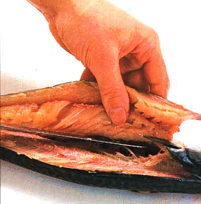 Continue cutting over the rib cage of the fish
